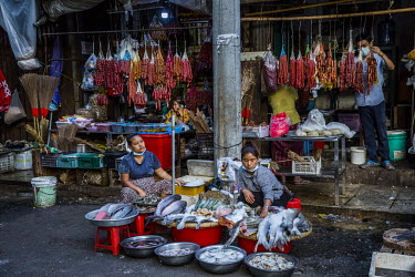 Two women sell fish in a market in downtown Yangon.