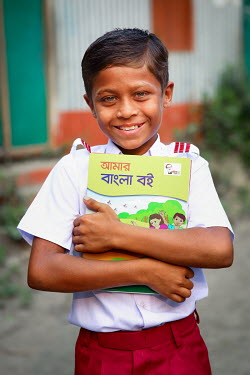A student wearing his new uniform, and proudly clutching his text books, on his first day at school after he was able to stop labouring work and attend school for the first time.