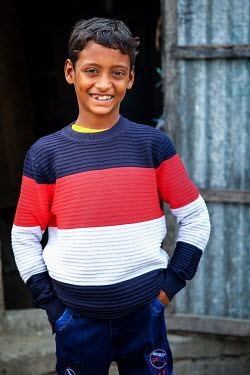 A boy wearing new clothes that were paid for by photographer G.M.B. Akash who is also sponsoring the boy so he has been able to stop labouring work and start to attend school for the first time.