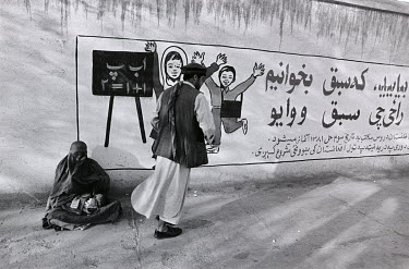 A man walks past a women begging at the roadside.