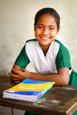 A student wearing her new uniform and sitting proudly at a desk with her text books, on her first day at school after she was able to stop labouring work and attend school for the first time.