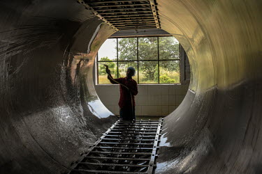 A worker cleans a steaming chamber at the Agave India factory, a craft distillery.