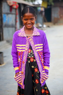 A girl wearing new clothes that were paid for by photographer G.M.B. Akash who is also sponsoring the girl so she has been able to stop labouring work and start to attend school for the first time.