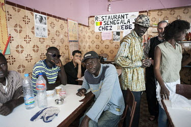 Mjiaye, a Senegalese migrant, sits at a table in Chez Kebe, a popular Senegalese restaurant. While making his way from Senegal to Europe, Mjiaye recently arrived in Tangier where he is trying to earn...