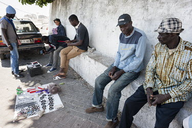 Mjiaye, a Senegalese migrant (in blue), sits at the entrance to the medina, where fellow African transit migrants sell bracelets. While making his way from Senegal to Europe, Mjiaye recently arrived i...