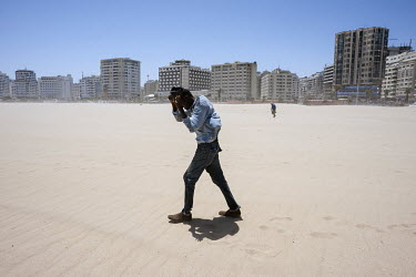 Mjiaye, a Senegalese migrant, braces against the wind blowing sand as he walks on the city's beach. While making his way from Senegal to Europe, Mjiaye recently arrived in Tangier where he is trying t...
