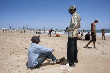 Mjiaye (in blue) and Medoune, Senegalese migrants, relax on the city's beach. While making his way from Senegal to Europe, Mjiaye recently arrived in Tangier where he is trying to earn some money in o...