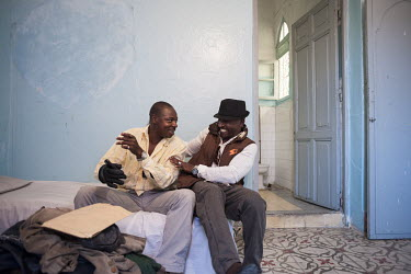 Nigerian migrants Sisi Collins Bacongu (left) and Winzo Asulu play and joke together while in their room in a cheap transit hotel in the medina. The pair are recently arrived in Tangier where they are...