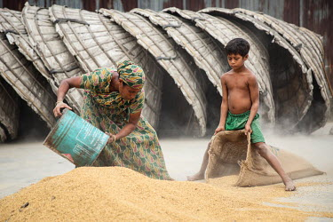 A child labourer helps a woman to fill sacks a grain mill before he was able to stop labouring and attend school.