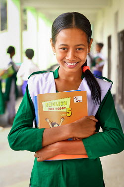 A student wearing her new uniform, and proudly clutching her text books, on her first day at school after she was able to stop labouring work and attend school for the first time.