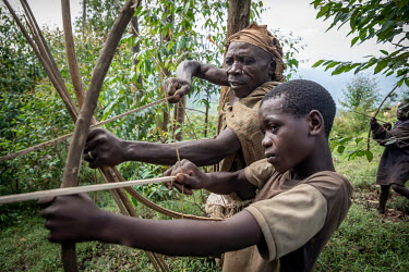 Francis Sembagare, a Batwa (pygmies) elder, teaches his child how to use a bow and arrow. Francis has known life in the rain forest, and tries to pass on old traditions, hunting techniques and knowled...