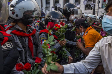 People offer red roses to riot police as they take part in a mass protest against the military coup of 1 February 2021 and in support of the NLD (National League for Democracy), Aung San Suu Kyi and d...
