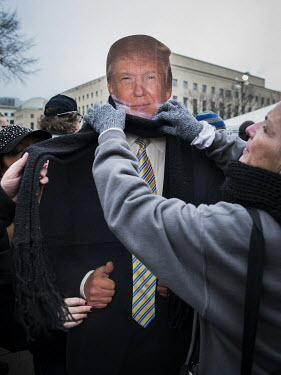 A person puts a scarf on a Trump cut out on the day of Donald Trump's inauguration.