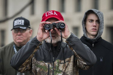 A man looks through a pair of binoculars on the day of Donald Trump's inauguration.