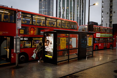 Buses at a stop in Elephant and Castle, during the 2021 COVID-19 lockdown, where a digital display carries a poster that is part of a campaign trying to promote compliance with coronavirus restriction...