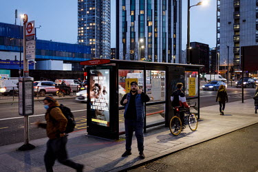 A man gives a 'thumbs up' while waiting at a stop in Elephant and Castle, during the 2021 COVID-19 lockdown, where a digital display carries a poster that is part of a campaign trying to promote compl...