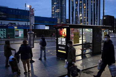 People wait at a bus stop at Elephant & Castle in London with a digital display board showing government Covid adivce.