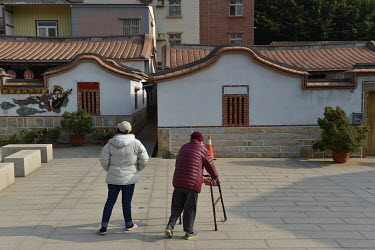 A foreign care worker (left) accompanies an elderly Kinmen resident on their daily exercises in Jincheng, Kinmen's main settlement.