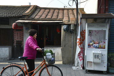 An elderly resident pushes her bicycle past a typical old house and a grabber game machine.