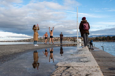 Winter swimmers head to the water along the Bains des Paquis jetty in Lake Geneva.