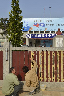 Workers paint a fence in front of the KMT (Kuomintang political party) HQ in downtown Jincheng.