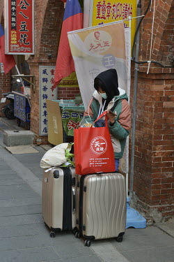 A domestic tourist with her luggage awaits transport on the Old Street in Jincheng, Kinmen's main settlement.