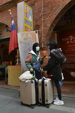 A domestic tourists with their luggage await transport on the Old Street in Jincheng, Kinmen's main settlement.