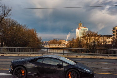 A sports car crosses a bridge over the Arve River with the RTS tower, the headquarters of the French language version of the Swiss national broadacaster, SSR, behind.