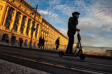 A youth rides an electric scooter past a parade of bank buildings facing the Rhone River.