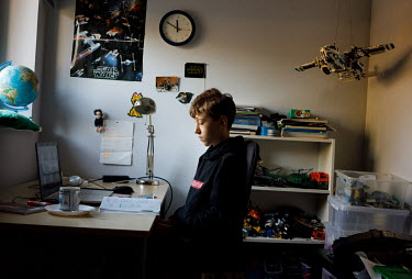 Mateusz, 12, a primary school student, at home during his online lessons. All lessons have been online since the pandemic began in March 2020.   'It is easier for me to focus on online classes, becaus...