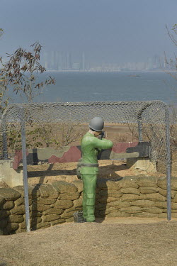 A manequin soldier keeps vigil on Xiao (Little) Kinmen Island against the risk of invasion from the Chinese mainland, visible in the distance a mile or two away.  Following the retreat of Chiang Kai-s...