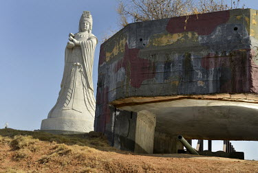 A statue of the Goddess Matzu (Mazu) beside an old artillery piece kept on display in a bunker on Xiao (Little) Kinmen Island, just a mile or two from the Chinese mainland.   Following the retreat o...