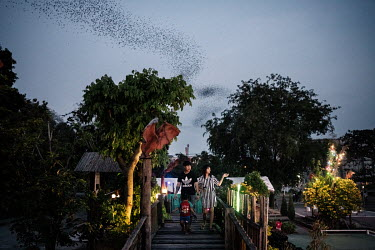 Visitors walk past a bat statue in a viewing area as millions of bats fly out of the Khao Chong Pran Cave.  A team of researchers consisting of scientists, ecologists, and officers from Thailand's Nat...