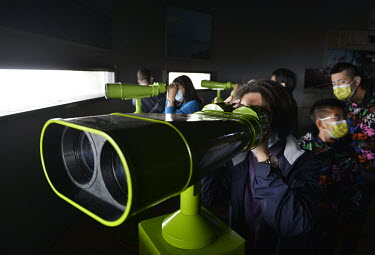 Taiwanese domestic tourists look at the coast of the Chinese mainland, just a few miles away, through high-powered binoculars at a military outpost on Xiao (Little) Kinmen.  Following the retreat of C...