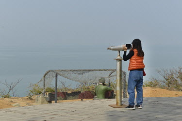 A domestic Taiwanese tourist looking through the wrong end of a tower viewer which is mounted at a view point on Xiao (Little) Kinmen Island looking towards the Chinese mainland. Beside the binocular...