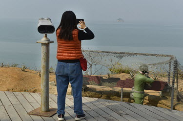 A domestic Taiwanese tourist takes a picture at a view point on Xiao (Little) Kinmen Island looking towards Shiyu Islet and the Chinese mainland. Beside the binocular stand is a manequin soldier also...