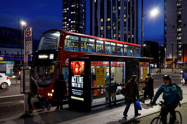 Travellers wait to enter a bus at a stop in Elephant and Castle with a digital display poster carrying a campaign to promote compliance with coronavirus restrictions, during the 2021 COVID-19 lockdown...