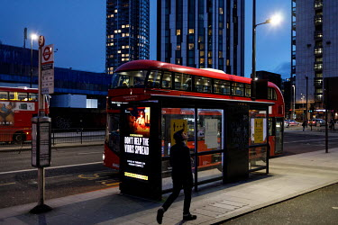 A bus at a stop in Elephant and Castle with a digital display poster, carrying a campaign to promote compliance with coronavirus restrictions during the 2021 COVID-19 lockdown, reminds people to 'Don'...