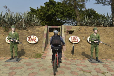A visitor rides a bicycle past soldier mannequins outside a coastal defensive post on on Xiao (Little) Kinmen Island, which is now more a tourist attraction for those curious about the Cold War.  Foll...