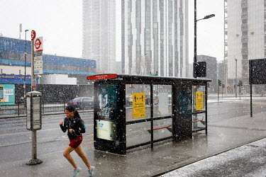 A woman runs past a bus stop in Elephant and Castle as the snow falls during the 2021 COVID-19 lockdown.