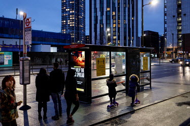 Travellers wait at a bus stop in Elephant and Castle with a digital display poster carrying a campaign to promote compliance with coronavirus restrictions, during the 2021 COVID-19 lockdown, reminds p...