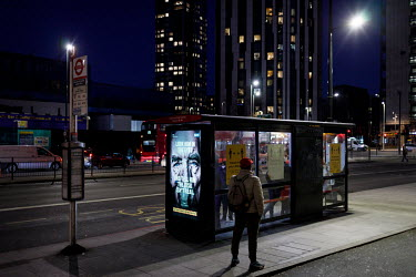 Travellers at a stop in Elephant and Castle, during the 2021 COVID-19 lockdown, where a digital display carries a poster that is part of a campaign trying to promote compliance with coronavirus restri...