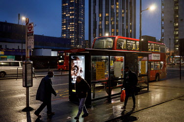 Travellers wait at a bus stop in Elephant and Castle, during the 2021 COVID-19 lockdown, where a digital display carries a poster that is part of a campaign trying to promote compliance with coronavir...