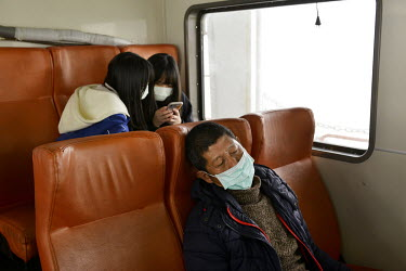 A man takes a nap during the short ferry ride from Kinmen's main island to Xiao (Little) Kinmen Island, just a mile or two from the Chinese mainland.   Following the retreat of Chiang Kai-shek's natio...