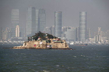Shiyu Islet, a forward observation post controlled by the Taiwanese military, and the gleaming skyscrapers of Xiamen on the Chinese mainland beyond, seen from Xiao (Little) Kinmen Island.  Following t...