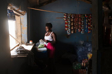 Helina Korley (20) working in her family's shop in the small village of Midie on the edge of the 'Yomo', the area traditionally held to be the spiritual heart of the salt-rich Songor Lagoon. A fashion...
