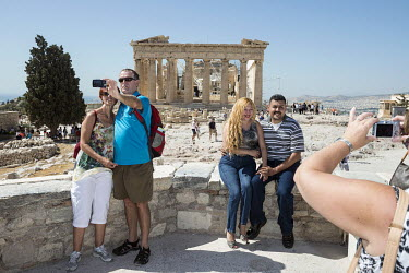 Tourists photograph each other in front of the Parthenon on the Acropolis.