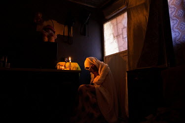 Addis Abeba Tirras, a Tigrayan woman, sits in front of a memorial for her brother killed during fighting in Tigray.