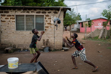 Noah Oletey (right) and a friend playing volleyball using a protruding roof beam as a net at in the village of Kpando Torkor.  Boat crew Noah Oletey (12) and his brother Vincent (14) spend up to six n...