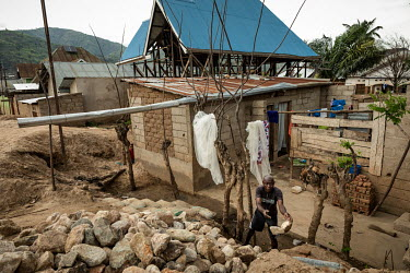 A man clears rocks from a building damaged by flooding after torrential rain caused the Mulongwe River to break its banks. The ensuing floods caused significant material damage with at least 3,500 hom...